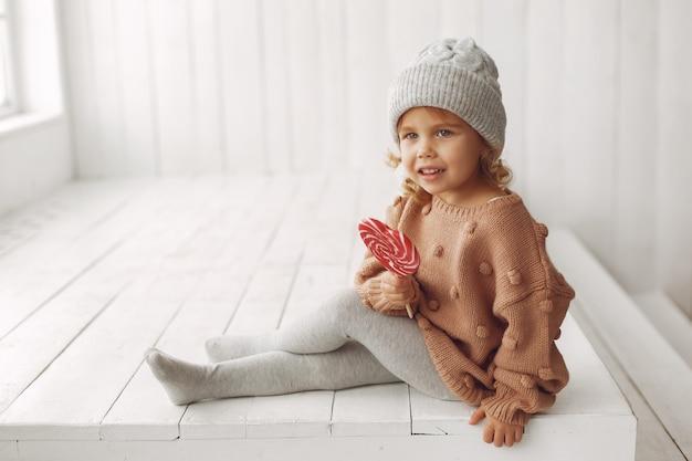座っているとお菓子を食べるかわいい女の子 無料写真