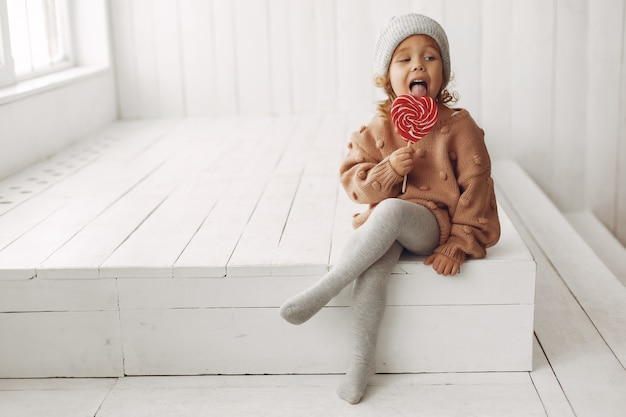 Милая маленькая девочка сидит и ест конфеты Бесплатные Фотографии