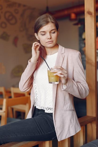 Элегантная женщина в розовой куртке проводит время в кафе Бесплатные Фотографии