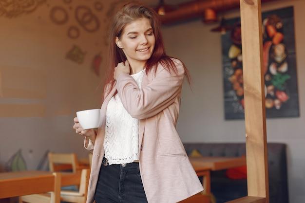カフェで時間を過ごすピンクのジャケットのエレガントな女性 無料写真