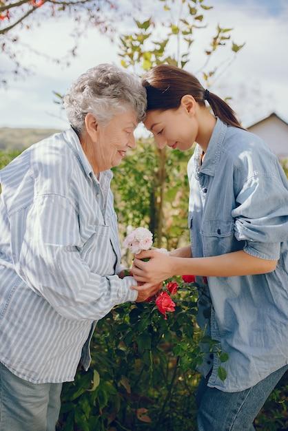 Старая женщина в саду с молодой внучкой Бесплатные Фотографии