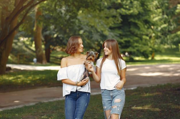 Милые девушки в парке играют с маленькой собачкой Бесплатные Фотографии