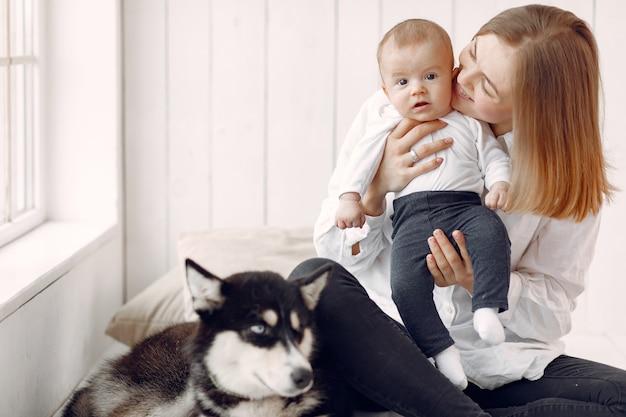 Мать и маленький сын, играя с собакой дома Бесплатные Фотографии