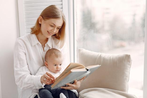 母と幼い息子が窓辺に座っています。 無料写真