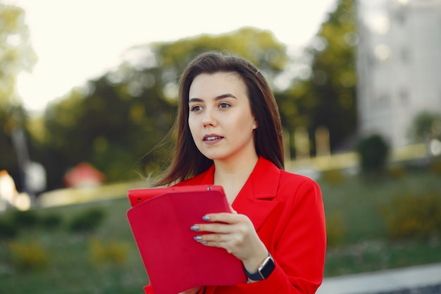 タブレットを使用して赤いジャケットの女性 無料写真