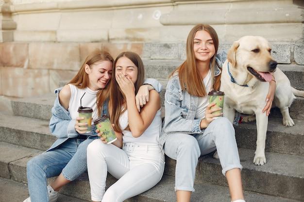 Девушки сидят на лестнице с милой собакой Бесплатные Фотографии