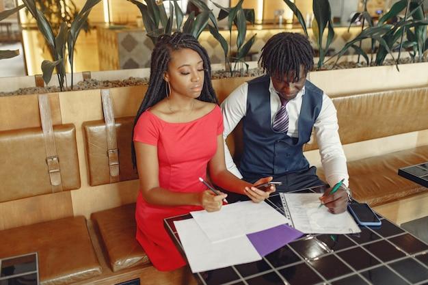 カフェに座っているとビジネス会話をするスタイリッシュな黒のカップル 無料写真