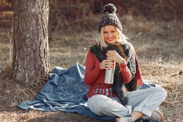 ドリンク魔法瓶と春の森の木に座っている女性 無料写真