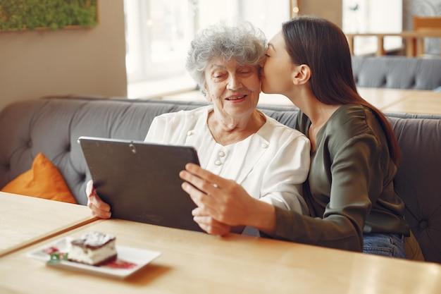 Девочка учит бабушку, как пользоваться планшетом Бесплатные Фотографии