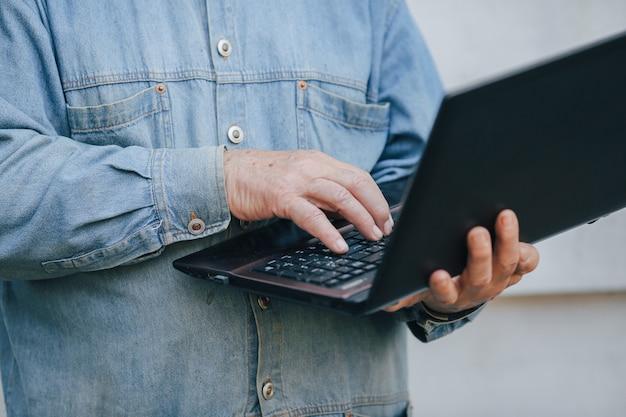 灰色の背景の上に立って、ラップトップを使用してエレガントな老人 無料写真