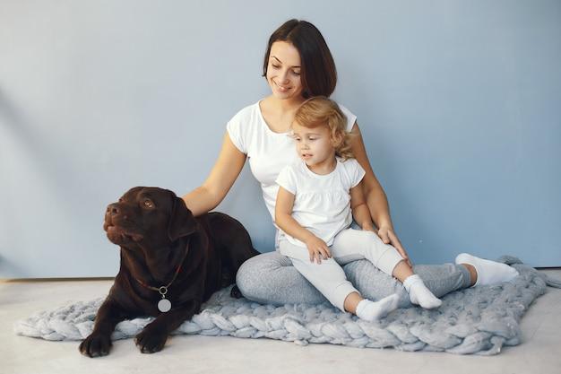 Мать и маленькая дочь, играя с собакой дома Бесплатные Фотографии