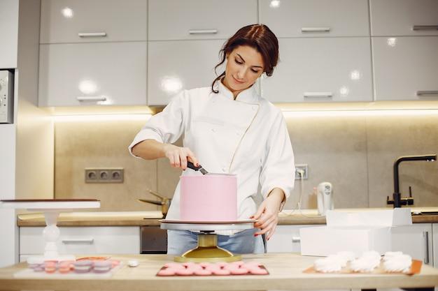 Кондитер в униформе украшает торт Бесплатные Фотографии