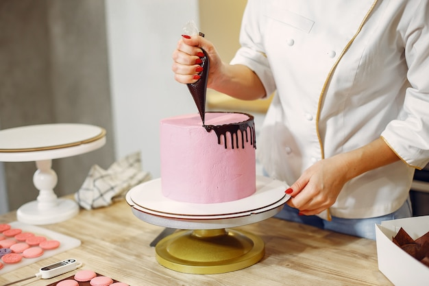 制服を着た菓子職人がケーキを飾る 無料写真