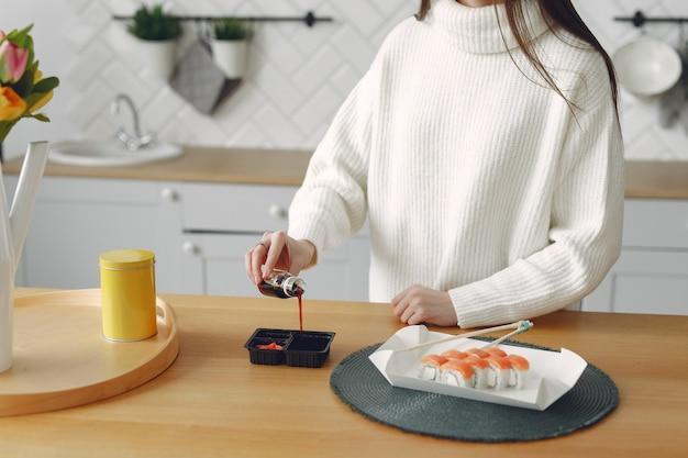 Девушка сидит дома за столом с суши Бесплатные Фотографии