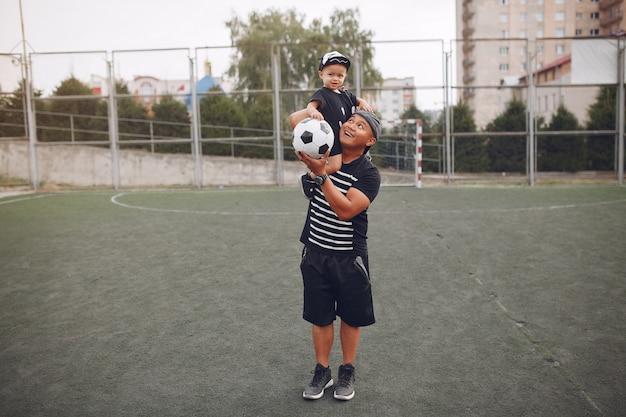 サッカーをしている幼い息子を持つ父 無料写真