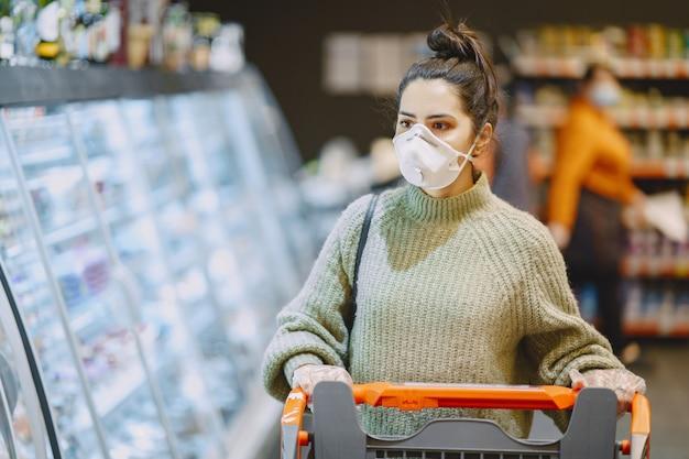 スーパーマーケットで防護マスクの女性 無料写真