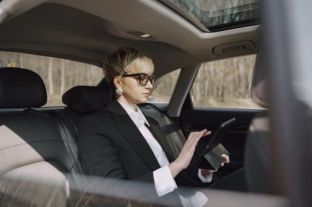 Коммерсантка сидя внутри автомобиля и использует таблетку Бесплатные Фотографии
