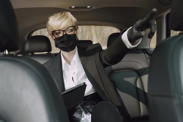 Деловая женщина в черной маске сидит в машине Бесплатные Фотографии