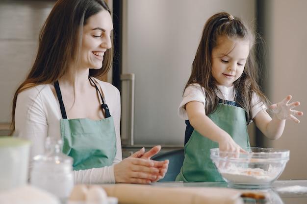 母と娘はクッキーのために生地を調理します 無料写真