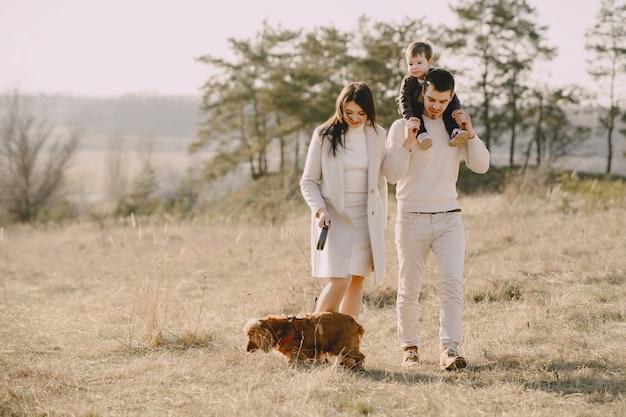 日当たりの良いフィールドの上を歩くスタイリッシュな家族 無料写真