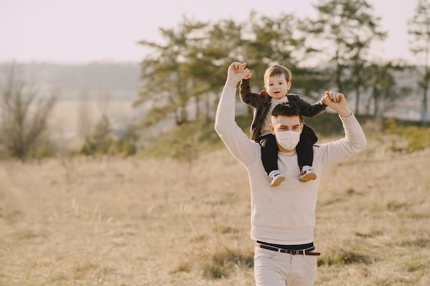 マスクを身に着けている幼い息子を持つ父 無料写真