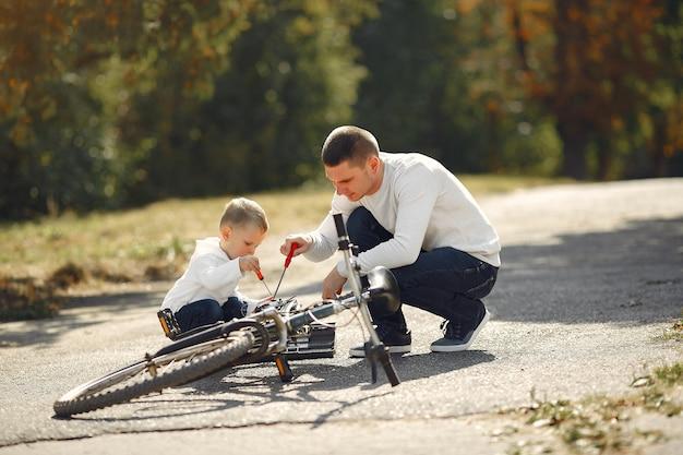 Отец с сыном ремонтируют велосипед в парке Бесплатные Фотографии