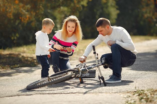 Семья с сыном ремонтируют велосипед в парке Бесплатные Фотографии