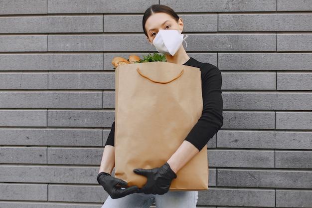 Девушка в защитной маске держит пакет с продуктами Бесплатные Фотографии