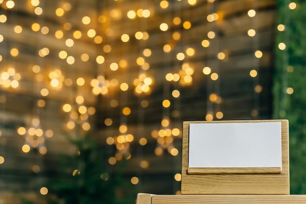 Пустой календарь - дневник на дубовой подставке белая карточка. против боке звезд гирлянды. Premium Фотографии