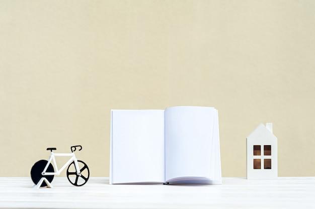 木製のテーブルの上に白い本、次は自転車でミニハウスです。 Premium写真