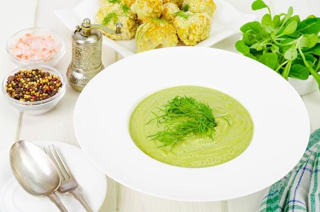 緑の野菜のクリームスープと白いプレート、健康的なダイエット料理。 Premium写真