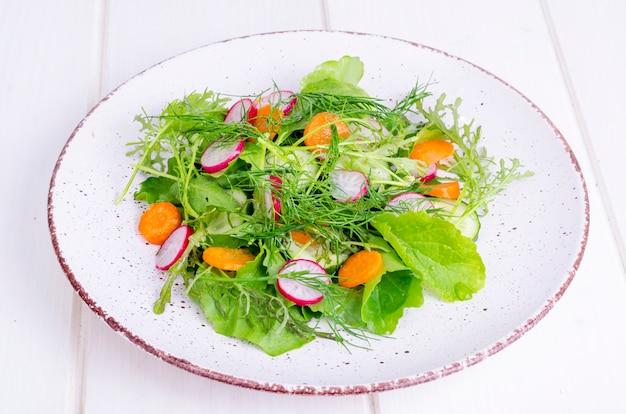 新鮮な野菜や白い皿にグリーンサラダの葉 Premium写真