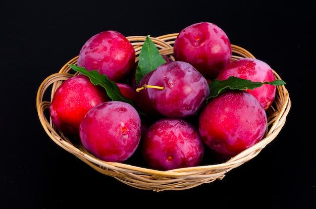 Спелые сладкие сливы в плетеной миске. фото Premium Фотографии