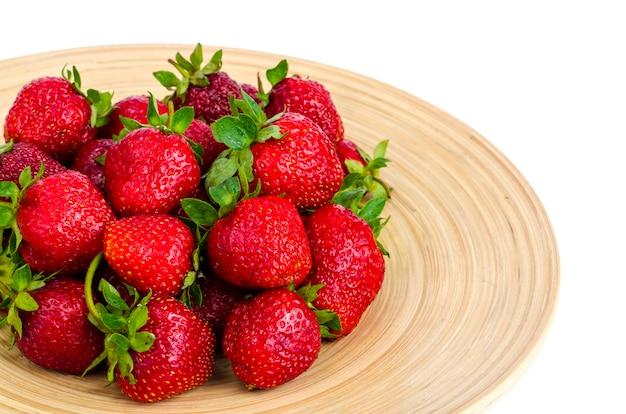 Спелый сладкий фермер красная клубника на деревянной тарелке Premium Фотографии