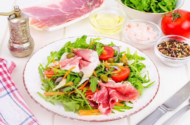 ルッコラ、ハモン、ルッコラ、トマト、パルメザンチーズと新鮮な自家製サラダ。 Premium写真