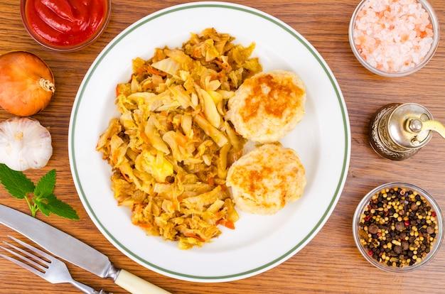 キャベツの煮込み、肉のカツレツ、スパイス、木製のテーブルの塩。 Premium写真