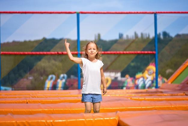Маленькая милая девушка имея потеху напольную прыжки на батуте в детской зоне. счастливая девушка прыгает на желтом батуте в парке развлечений Premium Фотографии