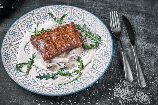 コンセプト:レストランメニュー、健康食品、自家製、グルメ、大食い。風化した木製のテーブルにステーキとキノコのソースとプレート。トップダウンビュー Premium写真