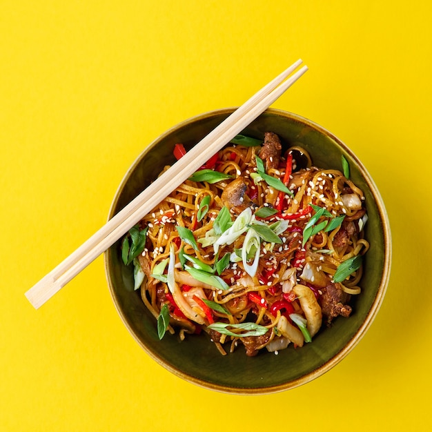 中華料理、肉入り麺鶏肉の炒め物と野菜醤油とごまの中華鍋。伝統的な中華料理。 Premium写真