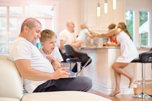 Сын с отцом сидят на диване, смотрят на ноутбук, на кухне мама, друзья и малыш Premium Фотографии