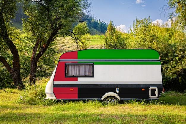 アラブ首長国連邦の国旗に描かれたトレーラー、キャンピングカーは山岳地帯に駐車されています。 Premium写真