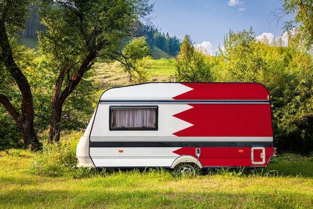 バーレーンの国旗に描かれたトレーラー、キャンピングカーは山岳地帯に駐車されています。 Premium写真