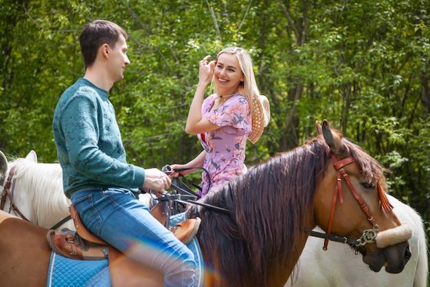 リンク花柄のドレスと自然に馬の上を歩く若い男で美しい少女。ライフスタイル気分。馬に乗ってデート愛好家 Premium写真