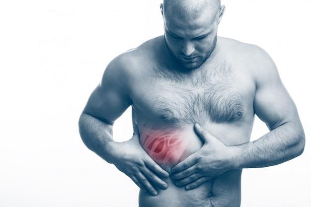 Молодой лысый мужчина спортивного телосложения держит на больном ребре Premium Фотографии
