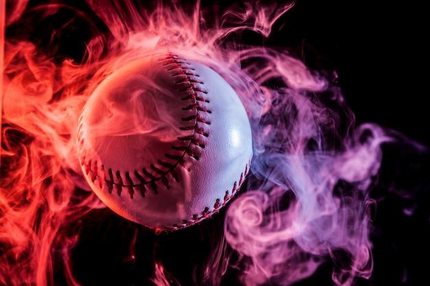 黒の孤立した背景にアークからマルチカラーの赤い煙で白い野球ボール Premium写真