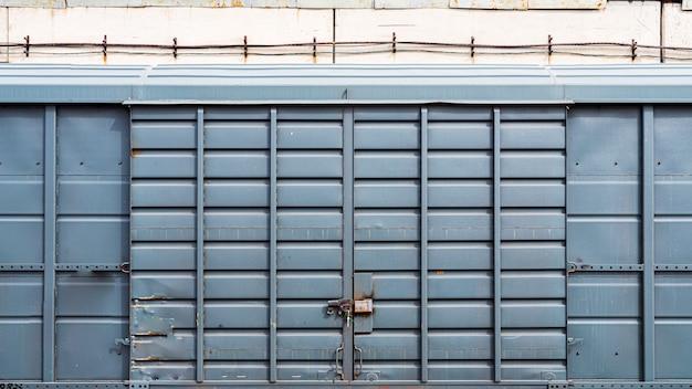 倉庫、ガレージにある大きな南京錠付きの古い金属製のドア。 Premium写真