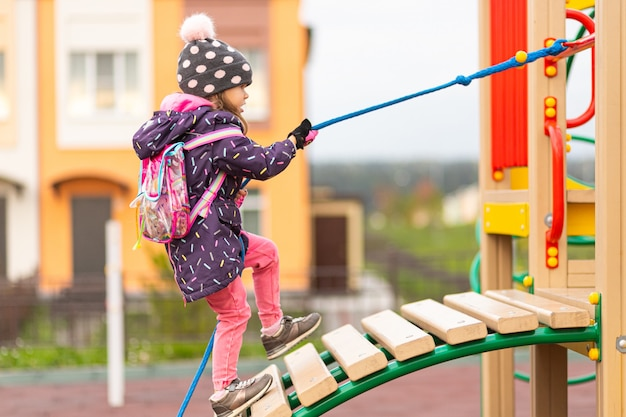 暖かいジャケット、帽子、面白いバックパックを着た面白い少女が、都市公園の遊び場でロープを使って木製の滑り台に登ります。 Premium写真