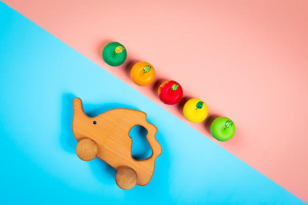 孤立した多色鮮やかな幾何学的な背景にカラフルなリンゴと木のおもちゃハリネズミ Premium写真