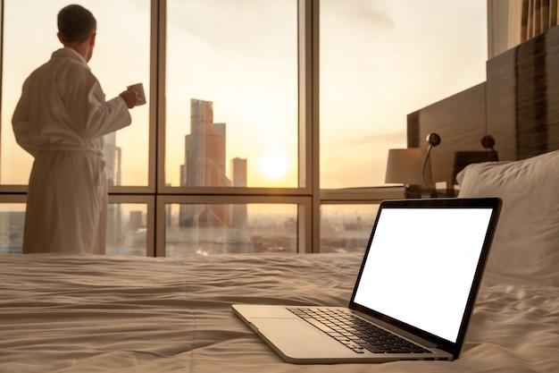 バスローブの背景の男とベッドの上でノートパソコンのクローズアップ 無料写真