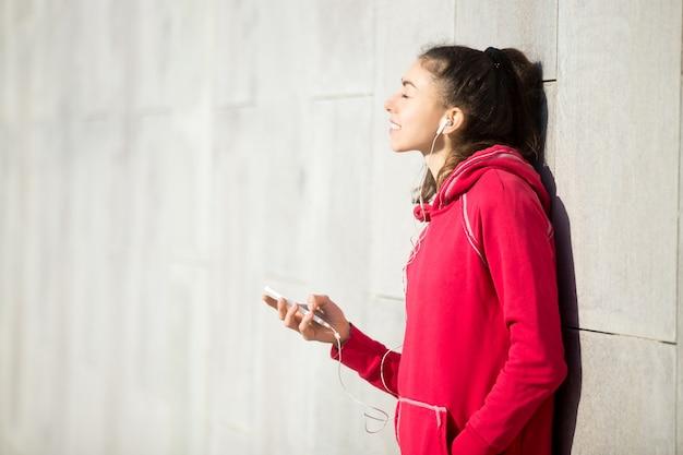 彼女の電話プレイヤーで音楽を楽しむ美しい女性 無料写真